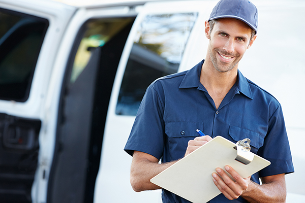 Portrait Of Delivery Driver With Clipboard Holding Pen Writing